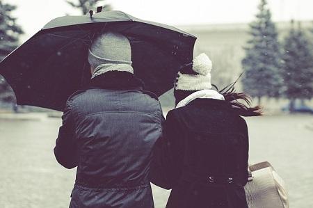 雨の日 カサを相合い傘の男女が、風雨に濡れて寒いイメージ