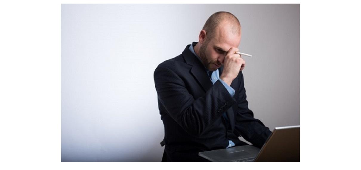 性がタバコをもって悩んでいる