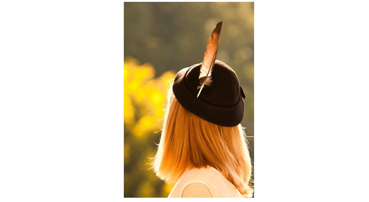 羽根つき帽子をかぶった女性