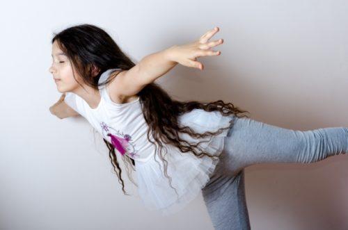 長髪の女の子が目をつぶって片足でバランスをとっている