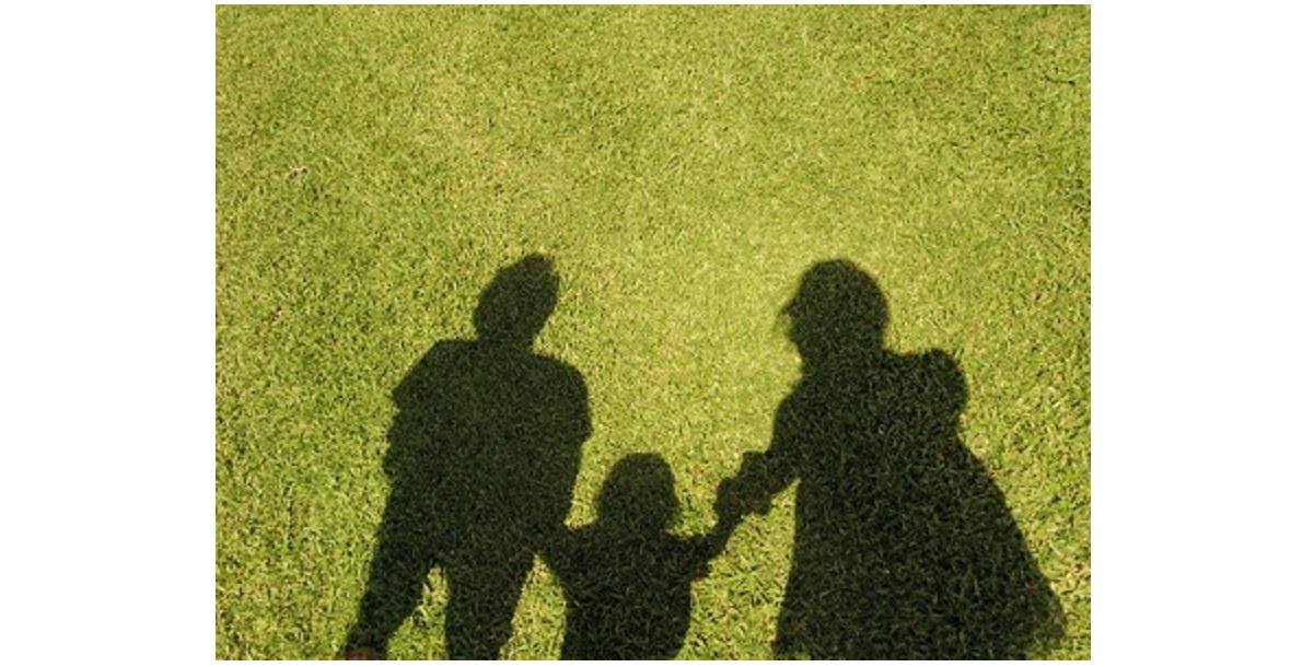 芝生に3人の親子の影