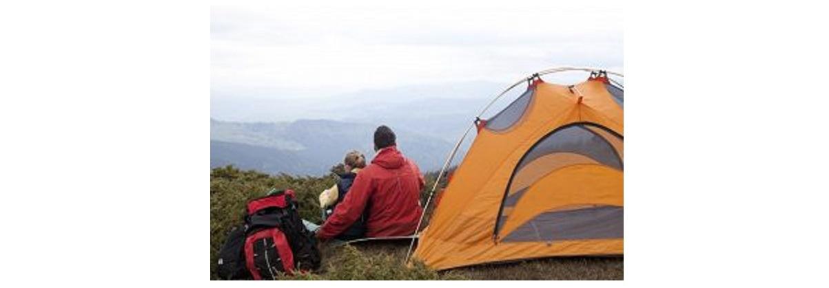 テントの脇で男女がもたれて座る