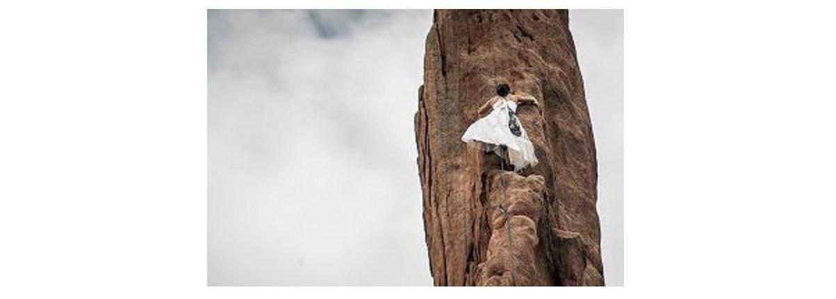 ウエディングドレスを着た女性がクライミング