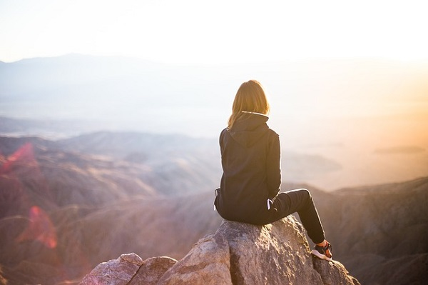 山の岩場に座る女性