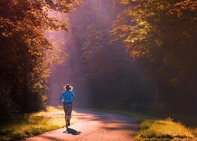 女性のjoggerが朝日の中を走っている