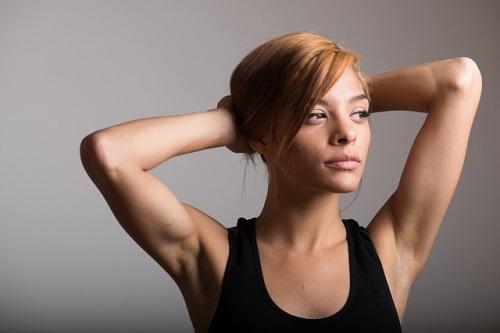 ユニクロスポーツ タンクトップを着た女性が頭に腕を組んでいる