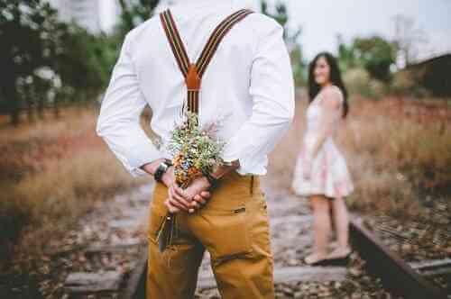 女性に花をプレゼントするために、後ろに花を隠している男性