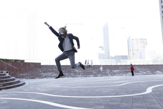 ライオンのマスクをしている男性が手を上げてジャンプ とてもうれしい様子