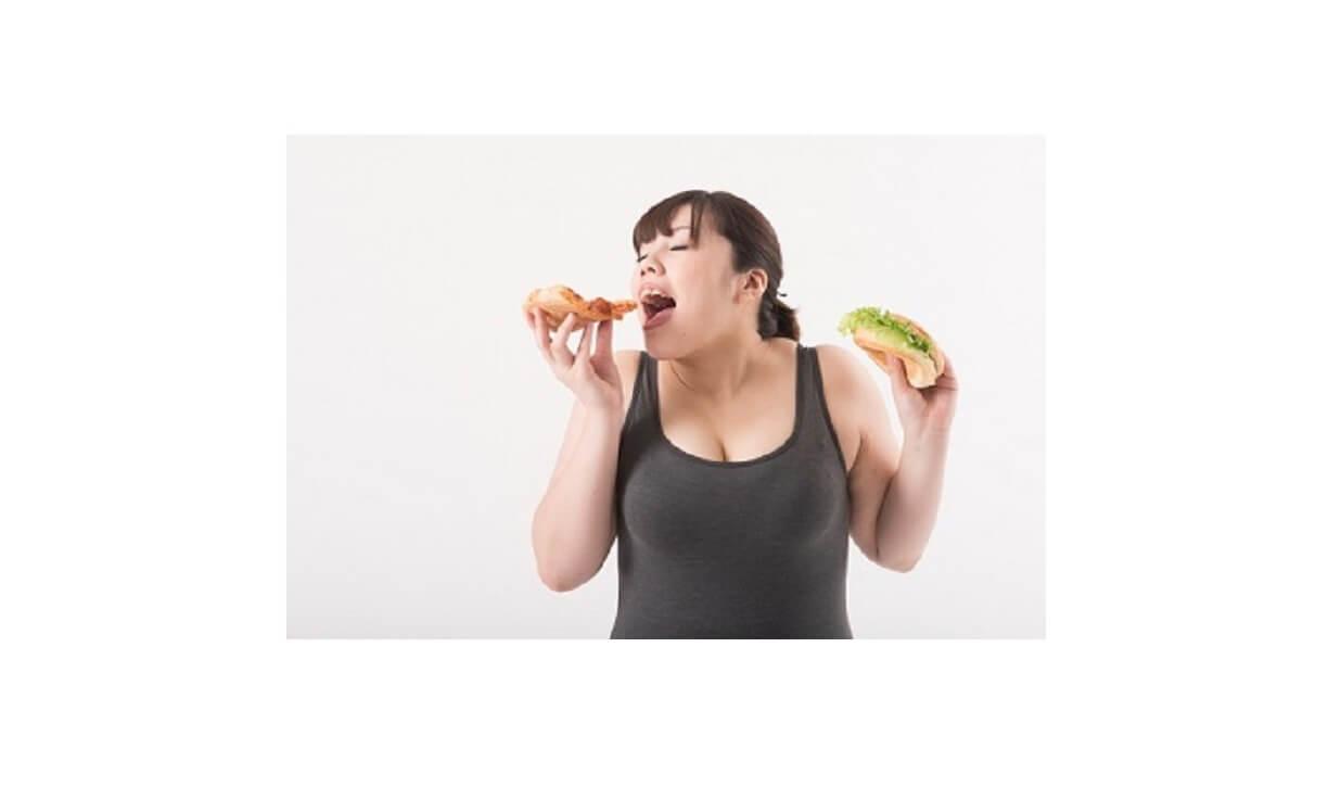 ふくよかな女性がホットドッグなどを食べまくっている