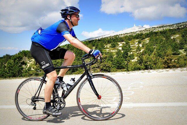 サングラスをかけてロードバイクで走る男性