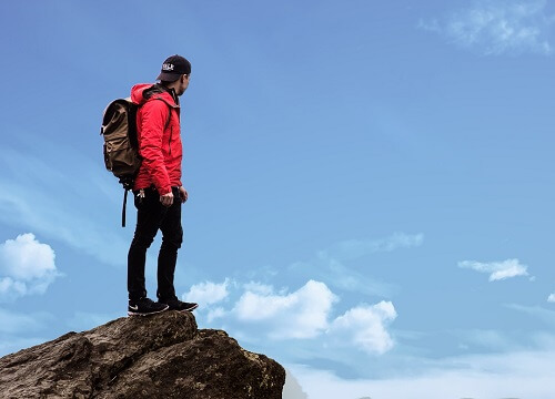 登山のアウタージャケットを着て山の上に立っている男性