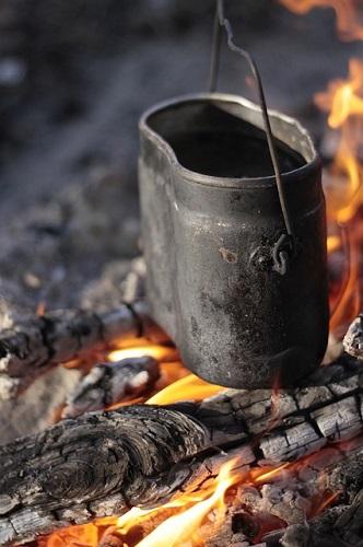 焚き火に古いコッヘルをかけている画像