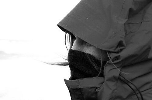 登山ウェアの選び方を間違えて風に耐える女性