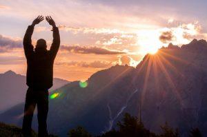 山から見える朝日を眺めている男性