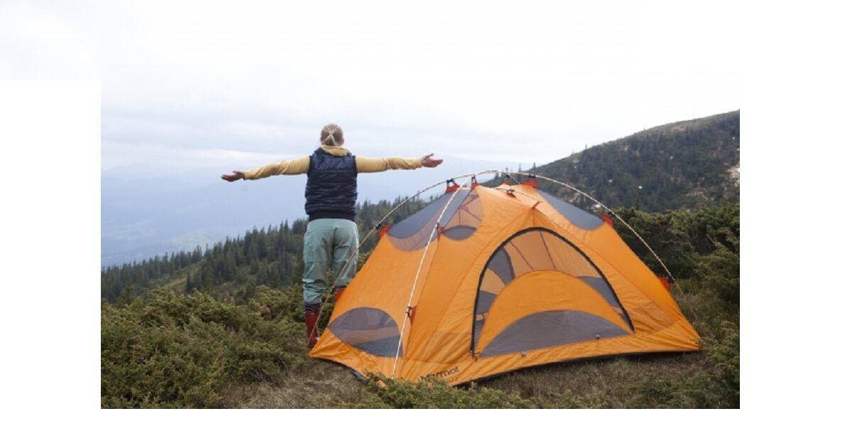 登山でシェルターの前で背伸びをする女性