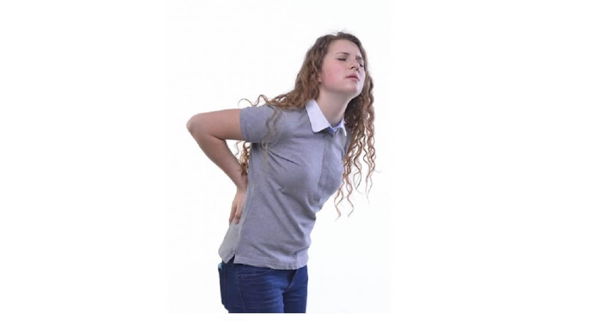 外国人の女性が腰痛で手で押さえる