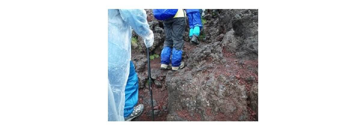 雨の中の登山で汚れたウェアを着て登っている人達