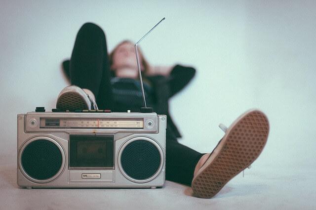 ラジオに足をかけて女性が聞いている