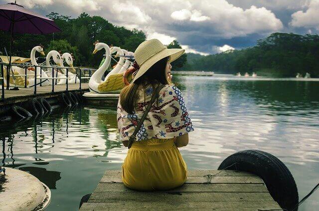湖畔でスカートをはいて座っている女性