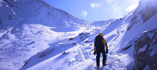 バラクラバをかぶって雪山登山をしている男性