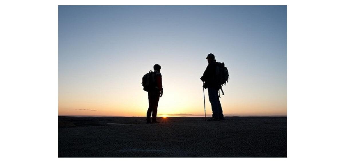 モンベルのトレッキングポールをもって朝日の中を登山をしている登山者2人